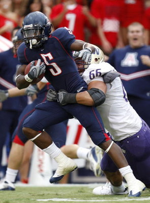 TUCSON, AZ - OCTOBER 04:  Nic Grigsby #5 of the Arizona Wildcats tries to escape the tackle of Daniel Te'o-Nesheim #66 of the Washington Huskies during a first quarter run on October 4, 2008 at Arizona Stadium in Tucson, Arizona.  (Photo by Gregory Shamus