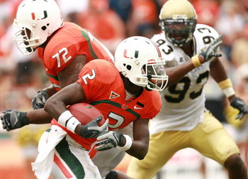 CORAL GABLES, FL - OCTOBER 13:  Running back Graig Cooper #2 of the Miami Hurricanes looks to get around defensive end Michael Johnson #93 of the Georgia Tech Yellow Jackets as he picks up a block from Andrew Bain #72 at the Orange Bowl on October 13, 200
