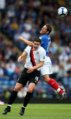 PORTSMOUTH, ENGLAND - AUGUST 30: Michael Brown of Portsmouth goes up for the ball against Gareth Barry of Manchester City during the Barclays Premier League match between Portsmouth and Manchester City at Fratton Park on August 30, 2009 in Portsmouth, Eng