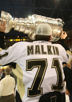 DETROIT - JUNE 12:  Evgeni Malkin #71 of the Pittsburgh Penguins celebrates with the Stanley Cup following the Penguins victory over the Detroit Red Wings in Game Seven of the 2009 NHL Stanley Cup Finals at Joe Louis Arena on June 12, 2009 in Detroit, Mic
