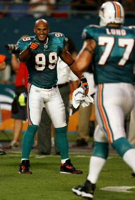 MIAMI - AUGUST 22:  Linebacker Jason Taylor #99 of the Miami Dolphins celebrates as he points to offensive lineman Jake Long #77 after a scoring drive against the Carolina Panthers during a pre-season game at Land Shark Stadium on August 22, 2009 in Miami