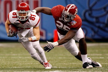 NEW ORLEANS - JANUARY 02:  Wide receiver Bradon Godfrey #81 of the Utah Utes runs after making a catch as he attempts to avoid a tackle by Rolando McClain #25 of the Alabama Crimson Tide in the first half during the 75th Allstate Sugar Bowl at the Louisia