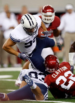 ARLINGTON, TX - SEPTEMBER 05:  Running back Bryan Kariya #33 of the Brigham Young Cougars is tackled by Keenan Clayton #22 of the Oklahoma Sooners at Cowboys Stadium on September 5, 2009 in Arlington, Texas.  (Photo by Ronald Martinez/Getty Images)