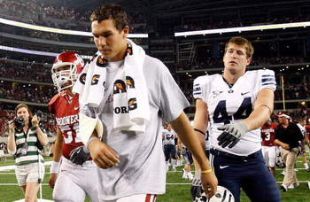 ARLINGTON, TX - SEPTEMBER 05:  Quarterback Sam Bradford #14 of the Oklahoma Sooners walks off the field past Jeremy Beal #44 after a 14-13 loss against the Brigham Young Cougars at Cowboys Stadium on September 5, 2009 in Arlington, Texas.  Bradford suffer
