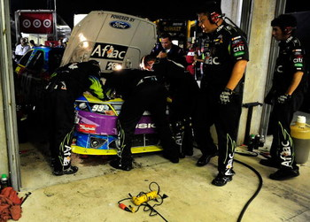 HAMPTON, GA - SEPTEMBER 06:  Crew members for Carl Edwards, driver of the #99 Aflac Cancer Center Ford, work on the car in the garage after having engine troubles during the NASCAR Sprint Cup Series Pep Boys Auto 500 at Atlanta Motor Speedway on September
