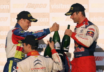 KINGSCLIFF, AUSTRALIA - SEPTEMBER 06:  Sebastien Loeb of France and the Citroen C4 Total team and Mikko Hirvonen of Finland and the BP Abu Dhabi Ford Focus team celebrate on the podium after the Repco Rally of Australia Special Stage 32 on September 6, 20
