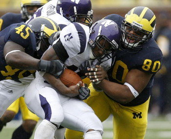 ANN ARBOR, MI - OCTOBER 28:  Terell Sutton #19 of the Northwestern Wildcats gets taken down by Alan Branch #80 and David Harris #45 of the Michigan Wolverines on October 28, 2006 at Michigan Stadium in Ann Arbor, Michigan. Michigan defeated Northwestern 1