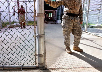 GUANTANAMO BAY, CUBA - JANUARY 20:  (NOTE TO EDITORS: PHOTO HAS BEEN REVIEWED BY US MILITARY OFFICIALS)  In this photo, reviewed by the U.S. Military, a guard leans on a fencepost as a Guantanamo detainee, left, jogs inside the exercise yard at Camp 5 det