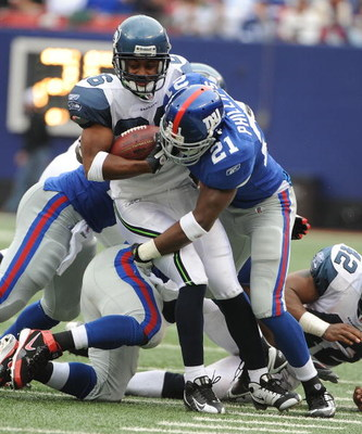 EAST RUTHERFORD, NJ - OCTOBER 05:  Kenny Phillips #21 of the New York Giants tackles Josh Wilson #26of the Seattle Seahawks during their game on October 5, 2008 at Giants Stadium in East Rutherford, New Jersey.  (Photo by Al Bello/Getty Images)