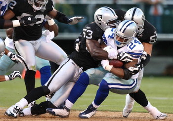 OAKLAND, CA - AUGUST 13:  Running back Marion Barber #24 of the Dallas Cowboys is tackled by Thomas Howard #53 and Ricky Brown #57 of the Oakland Raiders in the first quarter during the preseason game at Oakland-Alameda County Coliseum on August 13, 2009