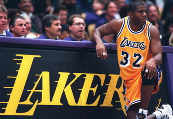 31 Jan 1996: Earvin Magic Johnson #32 of the Los Angeles Lakers kneels on the sidelines in his return to the NBA during the game against the Golden State Warriors at the Great Western Forum in Inglewood, California.