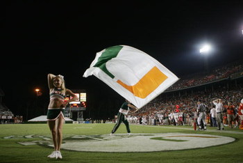 MIAMI - OCTOBER 14:  A male Miami Hurricanes cheerleader waves a giant flag while a female cheerleader performs during the game against the Florida International Panthers at the Orange Bowl on October 14, 2006 in Miami, Florida. Miami won 35-0.  (Photo by