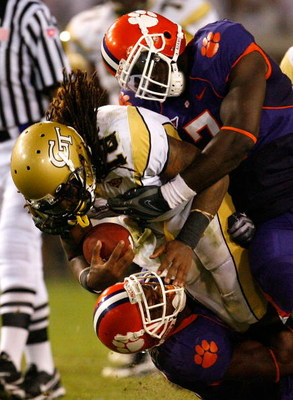 ATLANTA - SEPTEMBER 10:  Anthony Allen #18 of the Georgia Tech Yellow Jackets drives upfield against Ricky Sapp #7 and Marcus Gilchrist #12 of the Clemson Tigers  at Bobby Dodd Stadium on September 10, 2009 in Atlanta, Georgia.  (Photo by Kevin C. Cox/Get