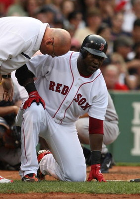 BOSTON - AUGUST 22:  David Ortiz #34 of the Boston Red Sox gets checked by the Red Soxs trainers after fouling a pitch off his ankle in the sixth inning against the New York Yankees at Fenway Park on August 22, 2009 in Boston, Massachusetts. (Photo by Jim