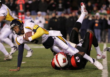 LOUISVILLE, KY - NOVEMBER 02:  Patrick White #5 of the West Virginia Mountaineers is tackled by Abe Brown #43 of the Louisville Cardinals November 2, 20006 at Papa John's Cardinal Stadium in Louisville, Kentucky.  (Photo by Andy Lyons/Getty Images)