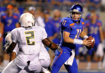 BOISE, ID - SEPTEMBER 3:  Kellen Moore #11 of the Boise State throws a pass under pressure by T.J. Ward #2 of the Oregon Ducks in second quarter of the game on September 3, 2009 at Broncos Stadium in Boise, Idaho. Boise State won the game 19-8. (Photo by