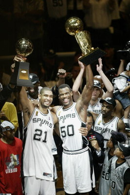 SAN ANTONIO - JUNE 15:  Tim Duncan #21 of the San Antonio Spurs holds up his NBA Finals MVP (Most Valuable Player) award as teammate David Robinson #50 holds up the 2003 NBA Championship trophy as the San Antonio Spurs celebrate in front of their fans aft