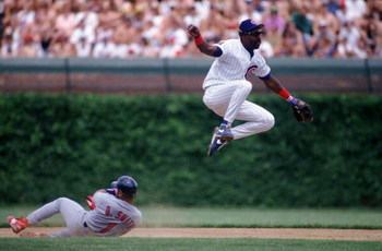 25 JUN 1994:  RUNNER OZZIE SMITH #1 OF THE ST. LOUIS CARDINALS SLIDES INTO SECOND BASE AS INFIELDER SHAWON DUNSTON OF THE CHICAGO CUBS TURNS A DOUBLE PLAY DURING THE CUBS 3-1 WIN AT WRIGLEY FIELD IN CHICAGO, ILLINOIS. Mandatory Credit: Jonathan Daniel/ALL