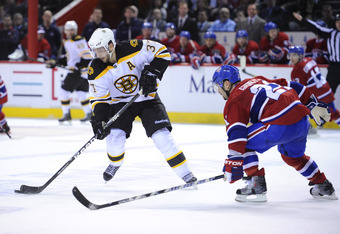MONTREAL, QC - APRIL 21:  Patrice Bergeron #37 of the Boston Bruins carries the puck up ice while being defended against by Brian Gionta #21 of the Montreal Canadiens in Game Four of the Eastern Conference Quarterfinals during the 2011 NHL Stanley Cup Pla