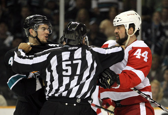 SAN JOSE, CA - MAY 01:  Marc-Edouard Vlasic #44 of the San Jose Sharks and Todd Bertuzzi #44 of the Detroit Red Wings are separated by lineman Jay Sharrers in Game Two of the Western Conference Semifinals during the 2011 NHL Stanley Cup Playoffs at HP Pav