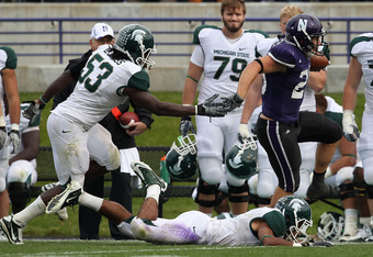EVANSTON, IL - OCTOBER 23: Mike Trumpy #29 of the Northwestern Wildcats runs past Greg Jones #53 (L) and Marcus Hyde #11 the Michigan State Spartans at Ryan Field on October 23, 2010 in Evanston, Illinois. Michigan State defeated Northwestern 35-27. (Phot