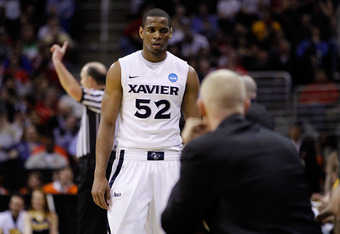 CLEVELAND, OH - MARCH 18: Tu Holloway #52 of the Xavier Musketeers walks to the bench late in the second half against the Marquette Golden Eagles during the second round of the 2011 NCAA men's basketball tournament at Quicken Loans Arena on March 18, 2011