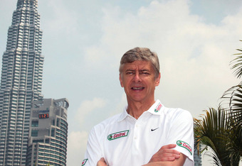 KUALA LUMPUR, MALAYSIA - JUNE 9:   Arsene Wenger poses for a portrait in front of Kuala Lumpurs landmark twin towersbefore taking the Malaysian youth team through the Castrol Challenge at the Dataran Merdeka Square during his tour of Asia with FIFA World
