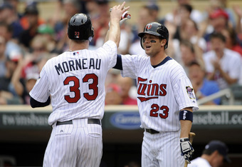 MINNEAPOLIS, MN - MAY 11: Justin Morneau #33 and Rene Tosoni #23 of the Minnesota Twins celebrates Morneau scoring against the Detroit Tigers during in the second inning of their game on May 11, 2011 at Target Field in Minneapolis, Minnesota. (Photo by Ha