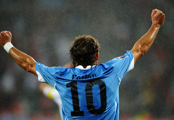 PORT ELIZABETH, SOUTH AFRICA - JUNE 26:  Diego Forlan of Uruguay celebrates team mate Luis Suarez scoring his second goal during the 2010 FIFA World Cup South Africa Round of Sixteen match between Uruguay and South Korea at Nelson Mandela Bay Stadium on J