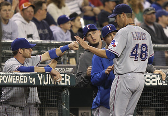 SEATTLE - JULY 15:  Starting pitcher Colby Lewis #48 of the Texas Rangers is congratulated by teammates after coming out of the game in the ninth inning against the Seattle Mariners at Safeco Field on July 15, 2011 in Seattle, Washington. The Rangers defe