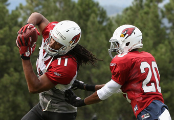 FLAGSTAFF, AZ - JULY 31:  Wide receiver Larry Fitzgerald #11 of the Arizona Cardinals makes a reception ahead of cornerback A.J. Jefferson #20 in the team training camp at Northern Arizona University on July 31, 2011 in Flagstaff, Arizona.  (Photo by Chri