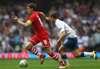 CARDIFF, WALES - MARCH 26: Aaron Ramsey of Wales takes the ball past Jack Wilshere of England during the UEFA EURO 2012 Group G qualifying match between Wales and England at the Millennium Stadium on March 26, 2011 in Cardiff, Wales.  (Photo by Alex Lives