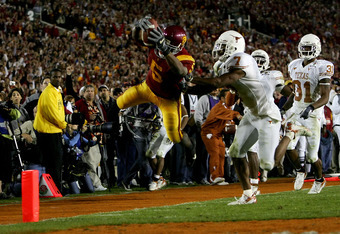 PASADENA, CA - JANUARY 04:  Reggie Bush #5 of the USC Trojans dives over the goal line as he scores a 26 yard touchdown in the fourth quarter of the BCS National Championship Rose Bowl Game against the Texas Longhorns at the Rose Bowl on January 4, 2006 i