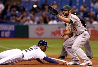 ST. PETERSBURG, FL - AUGUST 05:  Infielder Conor Jackson #28 of the Oakland Athletics takes the throw at first as B.J. Upton #2 of the Tampa Bay Rays gets back safely during the game at Tropicana Field on August 5, 2011 in St. Petersburg, Florida.  (Photo