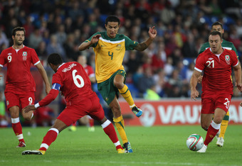 CARDIFF, WALES - AUGUST 10: Tim Cahill (C) of Australia evades the challenge from Ashley Williams (L) of Wales during the International Friendly match between Wales and Australia at the Cardiff City Stadium on August 10, 2011 in Cardiff, Wales.  (Photo by