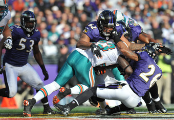 BALTIMORE, MD - NOVEMBER 7:  Terrence Cody #62 of the Baltimore Ravens tackles Ronnie Brown #23 of the Miami Dolphins at M&T Bank Stadium on November 7, 2010 in Baltimore, Maryland. The Ravens defeated the Dolphins 26-10. (Photo by Larry French/Getty Imag