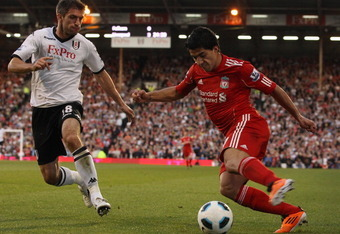 LONDON, ENGLAND - MAY 09:  Luis Suarez of Liverpool is challenged by Aaron Hughes of Fulham during the Barclays Premier League match between Fulham and Liverpool at Craven Cottage on May 9, 2011 in London, England.  (Photo by Scott Heavey/Getty Images)