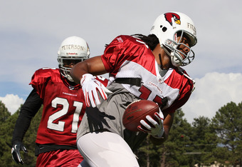 FLAGSTAFF, AZ - AUGUST 04:  Wide receiver Larry Fitzgerald #11 of the Arizona Cardinals catches a reception past cornerback Patrick Peterson #21 during the team training camp at Northern Arizona University on August 4, 2011 in Flagstaff, Arizona.  (Photo