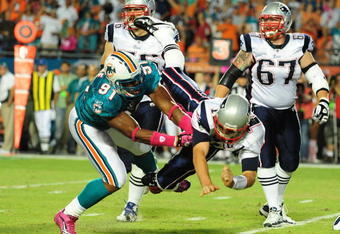 MIAMI - OCTOBER 4: Tom Brady #12 of the New England Patriots is hit after he passes by Cameron Wake #91 of the Miami Dolphins at Sun Life Field on October 4, 2010 in Miami, Florida. (Photo by Scott Cunningham/Getty Images)
