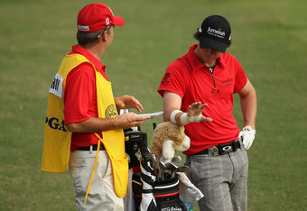 JOHNS CREEK, GA - AUGUST 11:  Rory McIlroy of Northern Ireland waits with his caddie J.P. Fitzgerald during the first round of the 93rd PGA Championship at the Atlanta Athletic Club on August 11, 2011 in Johns Creek, Georgia.  (Photo by Andrew Redington/G