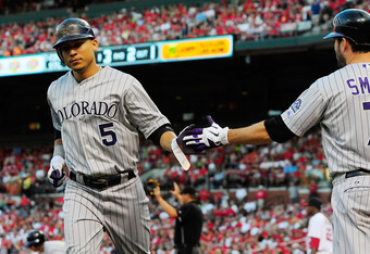 ST. LOUIS, MO - AUGUST 14: Carlos Gonzalez #5 of the Colorado Rockies is congratulated by Seth Smith #7 after scoring on a single by Troy Tulowitzki (not pictured) against the St. Louis Cardinals at Busch Stadium on August 14, 2011 in St. Louis, Missouri.