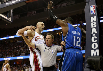 CLEVELAND - MAY 28: Referee Bill Spooner separates Zydrunas Ilgauskas #11 of the Cleveland Cavaliers and Dwight Howard #12 of the Orlando Magic after a play in Game Five of the Eastern Conference Finals during the 2009 Playoffs at Quicken Loans Arena on May 28, 2009 in Cleveland, Ohio. NOTE TO USER: User expressly acknowledges and agrees that, by downloading and or using this photograph, User is consenting to the terms and conditions of the Getty Images License Agreement  (Photo by Elsa/Getty Images)