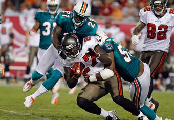 TAMPA, FL - AUGUST 27:  Running back LeGarrette Blount #27 of the Tampa Bay Buccaneers is tackled by defenders Karlos Dansby #58 and Vontae Davis #21 of the Miami Dolphins during a preseason game at Raymond James Stadium on August 27, 2011 in Tampa, Florida.  (Photo by J. Meric/Getty Images)