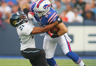 ORCHARD PARK, NY - AUGUST 27: Mike Caussin #82 of the Buffalo Bills is tackled by Derek Cox #21 of the Jacksonville Jaguars  at Ralph Wilson Stadium on August 27, 2011 in Orchard Park, New York.  (Photo by Rick Stewart/Getty Images)