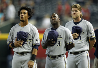 PHOENIX, AZ - JULY 20:  (L-R) Carlos Gomez #27,  Yuniesky Betancourt #3 and Corey Hart #3 of the Milwaukee Brewers stand attended for the National Anthem before the Major League Baseball game against the Arizona Diamondbacks at Chase Field on July 20, 2011 in Phoenix, Arizona. The Brewers defeated the Diamondbacks 5-2 in 10 innings.  (Photo by Christian Petersen/Getty Images)