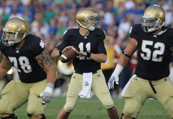 SOUTH BEND, IN - SEPTEMBER 03:  Tommy Rees #11 of the Notre Dame Fighting Irish looks for a receiver as Trevor Robinson #78 and Braxston Cave #52 move to block against the University of South Florida Bulls at Notre Dame Stadium on September 3, 2011 in Sou