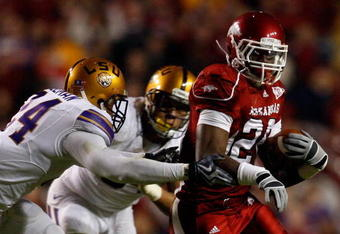 BATON ROUGE, LA - NOVEMBER 28:  Ronnie Wingo Jr. #20 of the Arkansas Razorbacks avoids a tackle by Harry Coleman #24 and Rahim Alem #84 of the LSU Tigers at Tiger Stadium on November 28, 2009 in Baton Rouge, Louisiana.  The Tigers defeated the Razorbacks