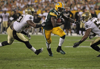 GREEN BAY, WI - SEPTEMBER 08: James Starks #44 of the Green Bay Packers runs between Junior Galette #93 and Jonathan Casillas #52 of the New Orleans Saints during the NFL opening season game at Lambeau Field on September 8, 2011 in Green Bay, Wisconsin. T