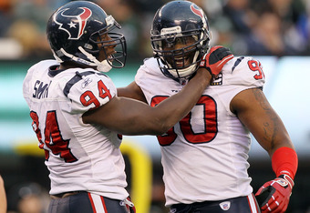 EAST RUTHERFORD, NJ - NOVEMBER 21: Mario Williams #90 of the Houston Texans celebrates a sack against the New York Jets with teammate Antonio Smith #94 on November 21, 2010 at the New Meadowlands Stadium in East Rutherford, New Jersey. The Jets defeated t