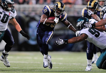 ST. LOUIS, MO - SEPTEMBER 11: Cadillac Williams #33 of the St. Louis Rams runs and pushes off of Cullen Jenkins #97 of the Philadelphia Eagles at the Edward Jones Dome on September 11, 2011 in St. Louis, Missouri. The Eagles defeated the Rams 31-15. (Phot